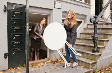 deux femmes portant une table de jardin blanche à la sortie d'un immeuble