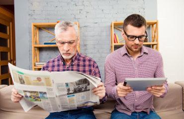 père lit un journal, le fils lit sur sa tablette