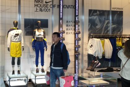client sortant de la boutique Nike House of Innovation à Shanghai avec un sac d'achats